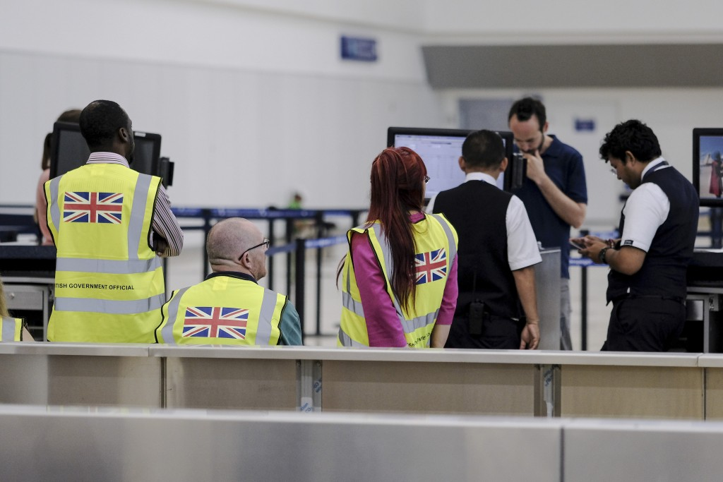 British government officials wait for stranded British passengers at the Cancun airport in Mexico, Monday, Sept. 23, 2019. British tour company Thomas...