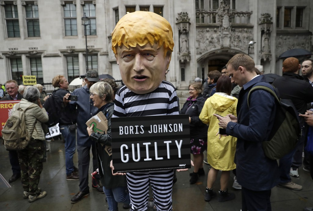 A person dressed as a caricature of British Prime Minister Boris Johnson in a prison uniform stands outside the Supreme Court in London, Tuesday, Sept...
