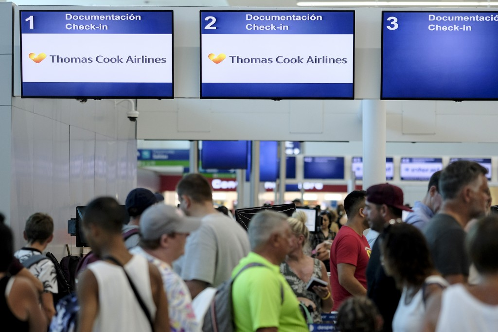 Stranded tourists line up in front of the Thomas Cook counter at the Cancun airport in Mexico, Monday, Sept. 23, 2019. British tour company Thomas Coo...