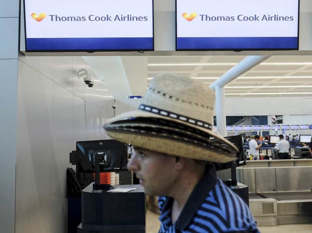A tourist walks past a Thomas Cook counter at the Cancun airport in Mexico, Monday, Sept. 23, 2019. British tour company Thomas Cook collapsed early M...