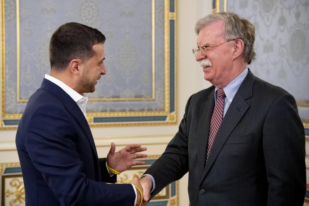 FILE - In this file photo taken on Aug. 28, 2019, John Bolton, U.S. National Security Advisor, right, is welcomed Ukrainian President Volodymyr Zelens...