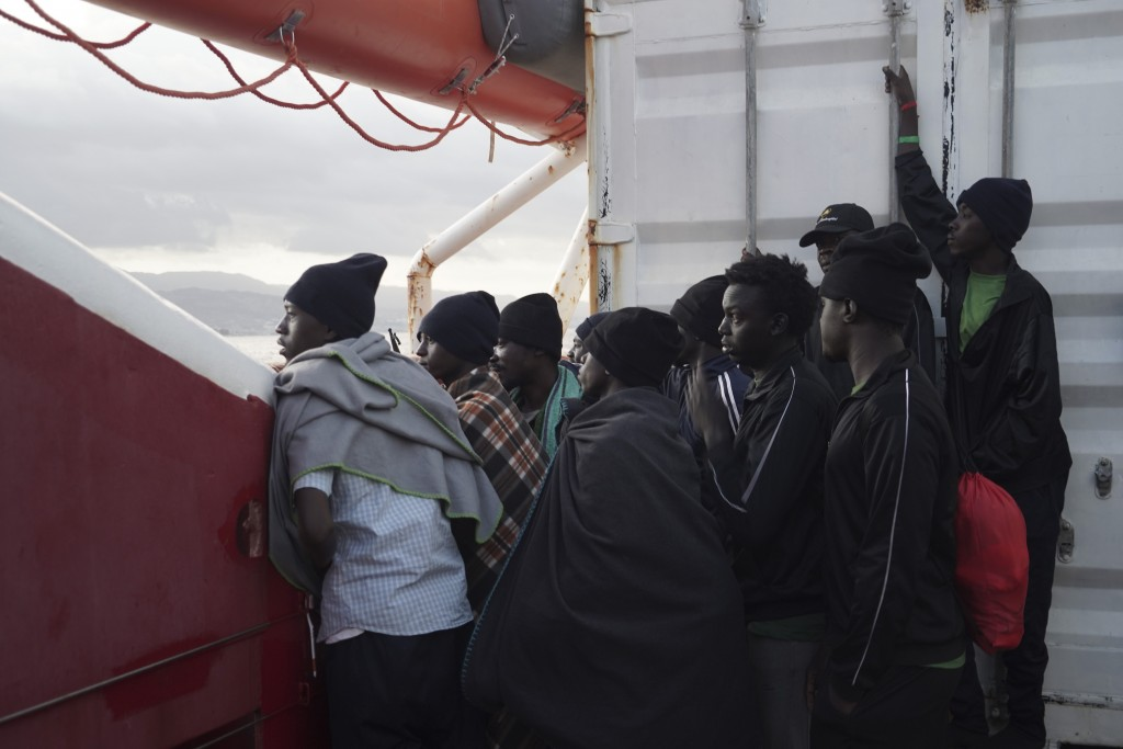 Men wait to disembark from the Ocean Viking ship as it reaches the port of Messina, Italy, Tuesday, Sept. 24, 2019.  The humanitarian ship has docked ...