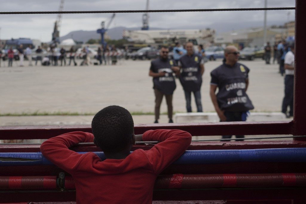 A little boy looks at police from aboard the Ocean Viking in the Mediterranean Sea, Tuesday, Sept. 24, 2019. He was among 182 people aboard the Ocean ...