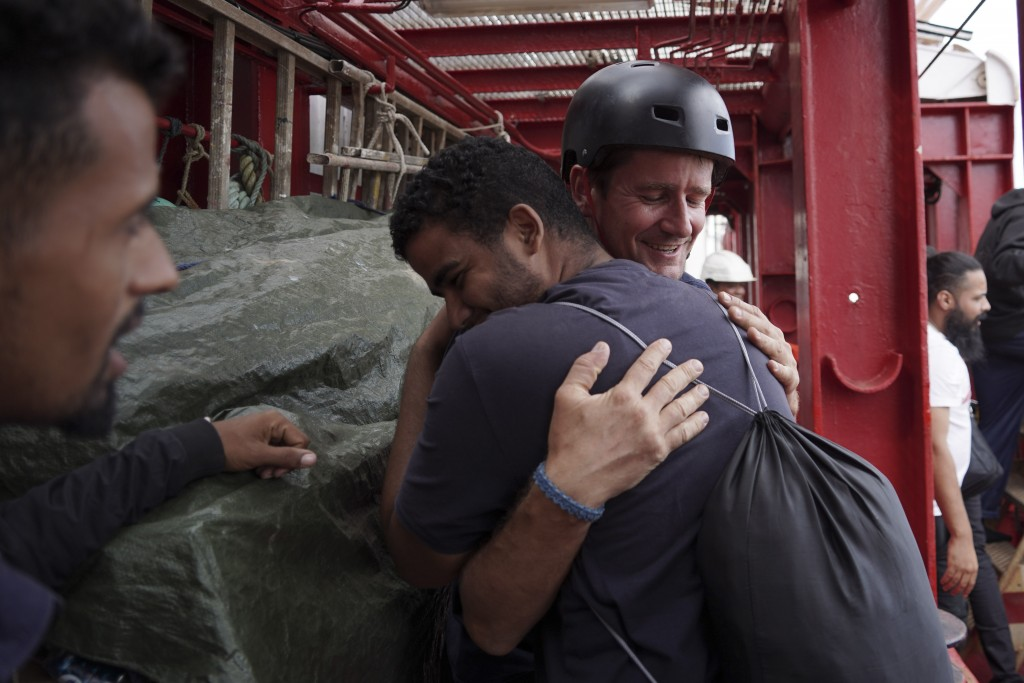 A migrant hugs an SOS Mediterranee rescuer aboard the Ocean Viking ship before stepping into the port of Messina, Italy, Tuesday, Sept. 24, 2019. He w...