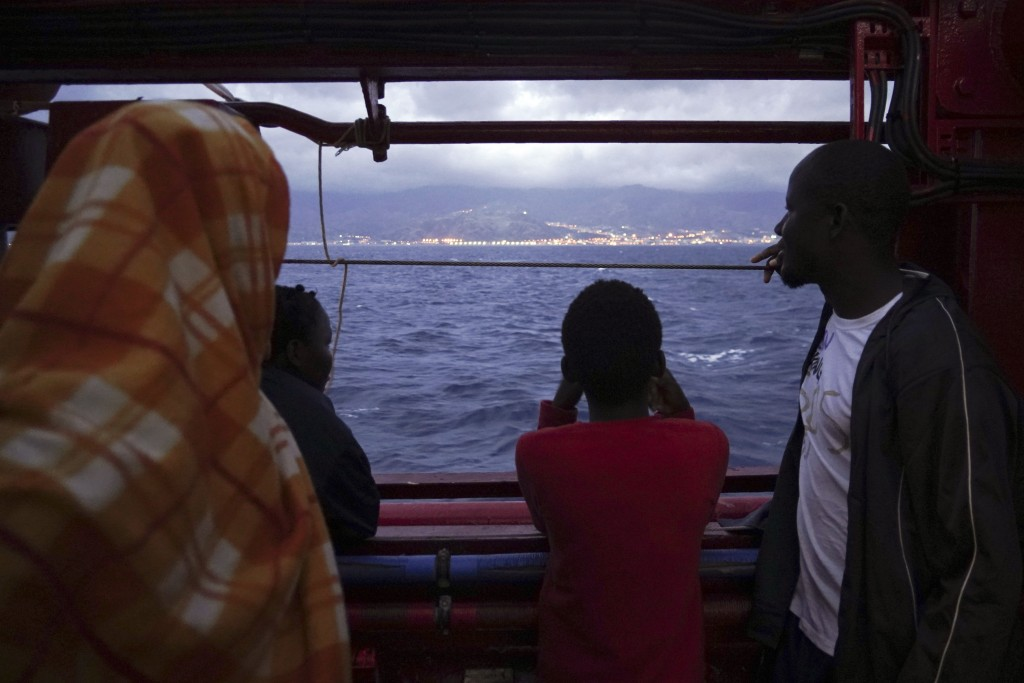 Migrants look at the Italian shoreline from aboard the Ocean Viking as it approaches the Sicilian port of Messina, southern Italy, Tuesday, Sept. 24, ...