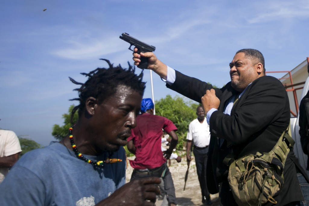 Ruling party Senator Ralph Fethiere fires his gun outside Parliament as he arrives for a vote on the ratification of Fritz William Michel's nomination...