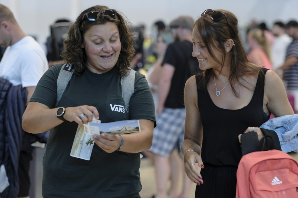 Tourists smile after checking in an alternate flight, at the Cancun airport in Mexico, Monday, Sept. 23, 2019. British tour company Thomas Cook collap...