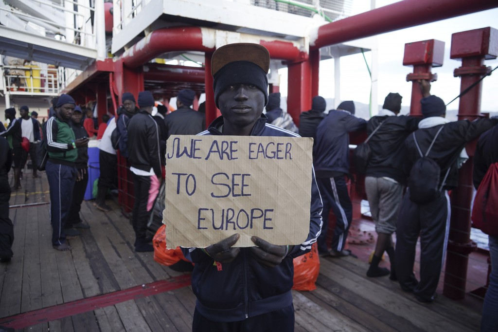 """A man shows a banner reading """"We are eager to see Europe"""" before disembarking from aboard the Ocean Viking ship as it reaches the port of Messina, Ita..."""