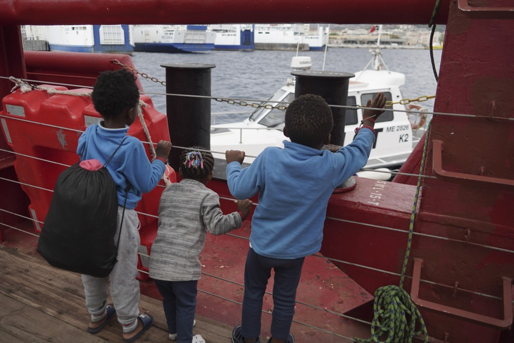Children wave at a boat from aboard the Ocean Viking as it reaches the port of Messina, Italy, Tuesday, Sept. 24, 2019. The humanitarian ship has dock...