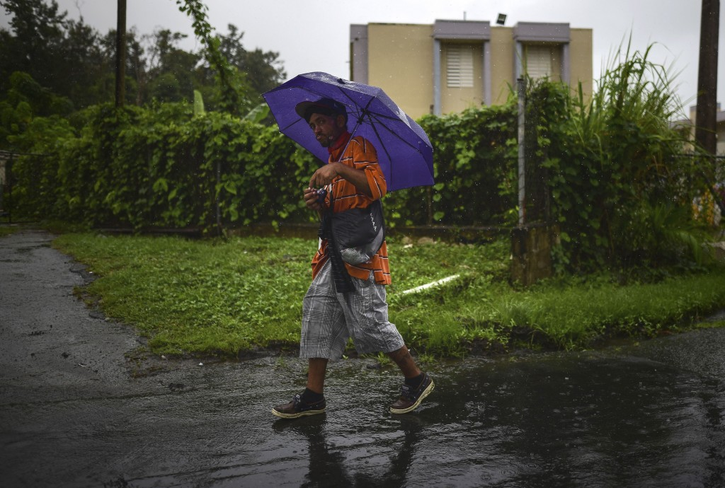 A man walks in the rain in Yabucoa, before the arrival of Tropical Storm Karen, in Yabucoa, Puerto Rico, Tuesday, Sept. 24, 2019. Karen regained tropi...