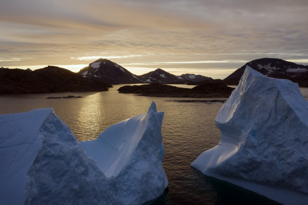 FILE - This early Friday, Aug. 16, 2019 file photo shows an aerial view of large Icebergs floating as the sun rises near Kulusuk, Greenland. Greenland...