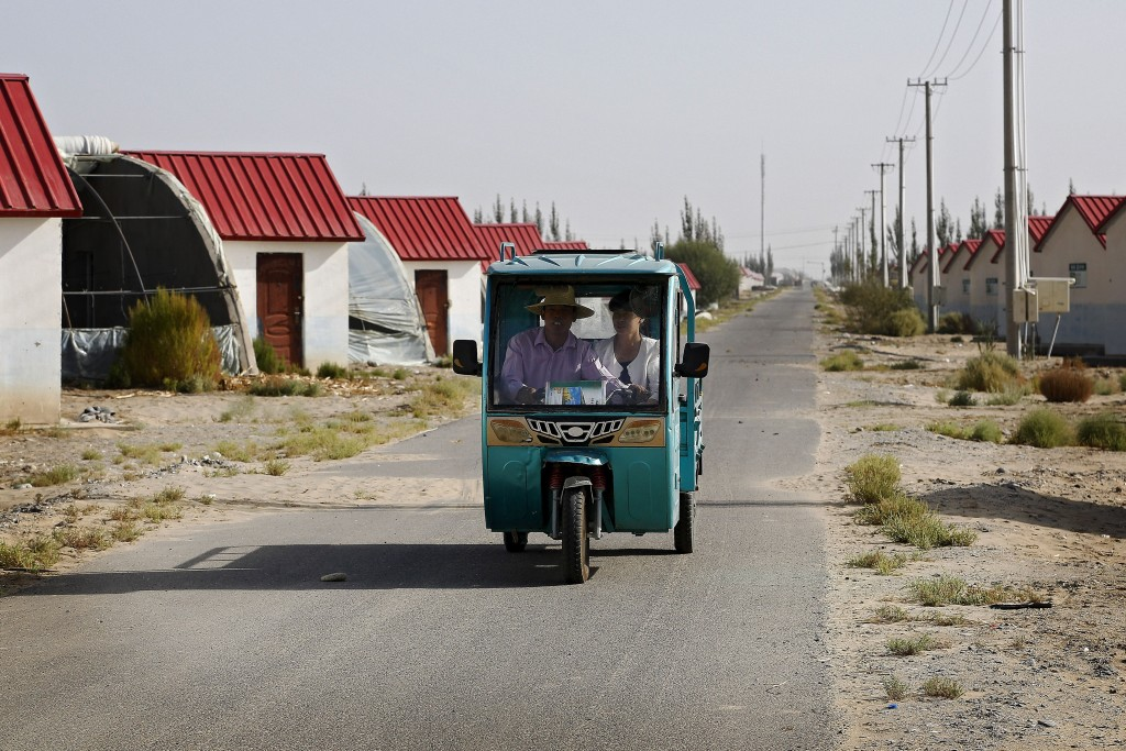 In this Sept. 21, 2018, photo, Han Chinese ride in a tricycle passing by farmhouses at the Unity New Village in Hotan, in western China's Xinjiang reg...