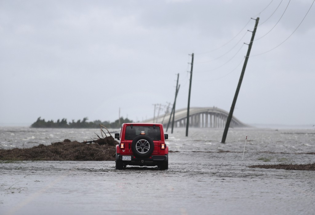 FILE - In this Friday, Sept. 6, 2019 file photo, storm surge from Hurricane Dorian blocks Cedar Island off from the mainland on NC 12 in Atlantic Beac...