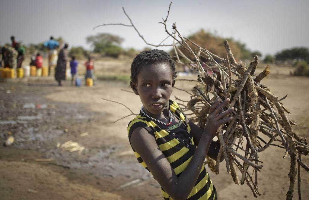 FILE - In this Thursday, Jan. 2, 2014 file photo, a displaced girl returns from gathering firewood while others, left, extract water from a well, some...