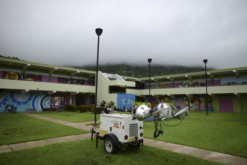 A portable light pole sits parked in a courtyard of Ramon Quinones Medina High School, where residents can seek temporary shelter, as residents prepar...