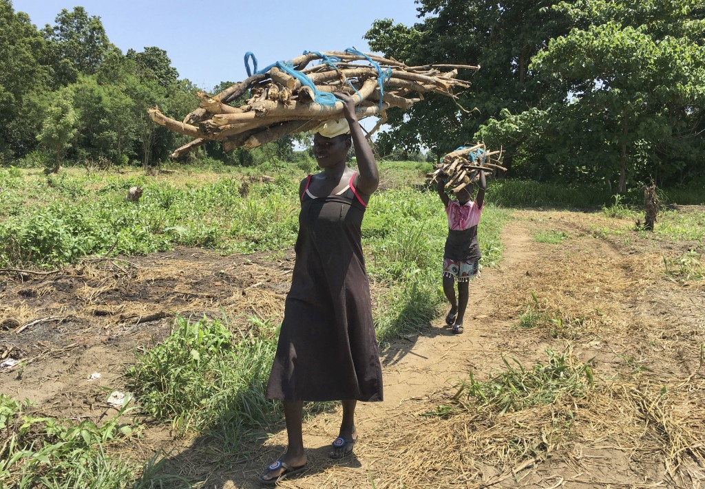 FILE - In this Friday, July 14, 2017 file photo, a woman and her daughter walk home with firewood in the small town of Rajaf, near Juba, in South Suda...