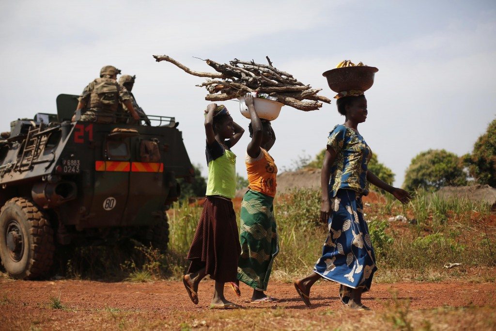 FILE - In this Monday, Feb. 10, 2014 file photo, women carrying wood walk past a French military patrol 10 kms south of Yaloke, north of Bangui, in Ce...