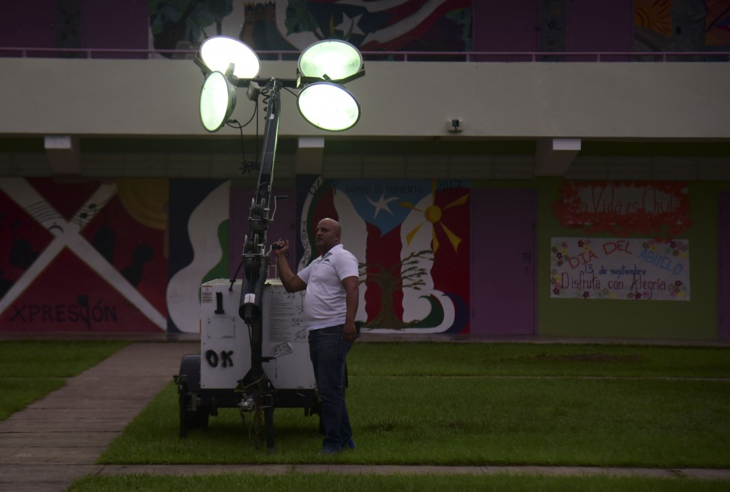 A municipal worker turns on portable lights atthe inner courtyard of Ramon Quinones Medina High School, one of the shelters enabled by the municipalit...