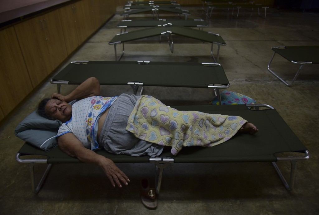 Luz Aponte Velazquez lies on a cot at the Ramon Quinones Medina High School, one of the shelters enabled by the municipality of Yabucoa, before the ar...