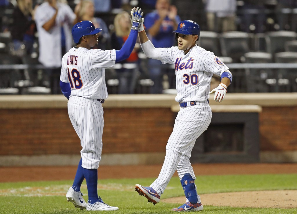 New York Mets' Rajai Davis greets Michael Conforto after scoring on Conforto's game-tying, two-run home run during the ninth inning of the team's base...