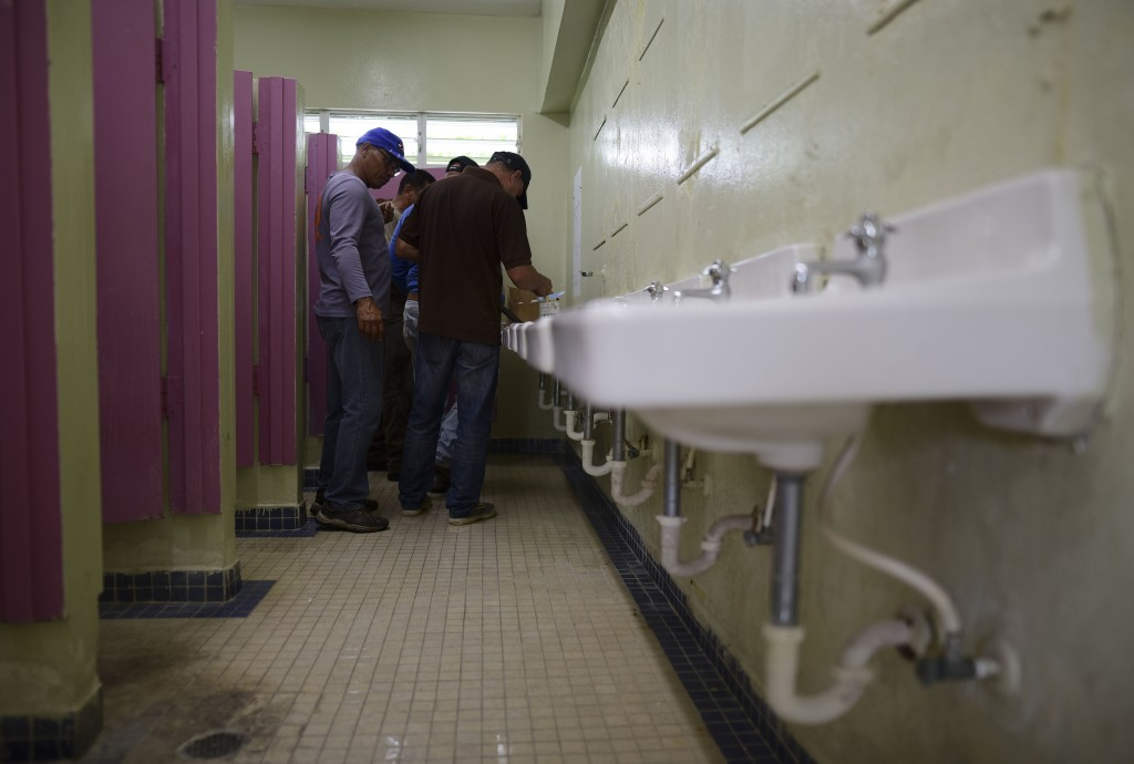 Municipal workers install a shower system in a bathroom at the Ramon Quinones Medina High School, being prepped as a temporary shelter, in Yabucoa, Pu...