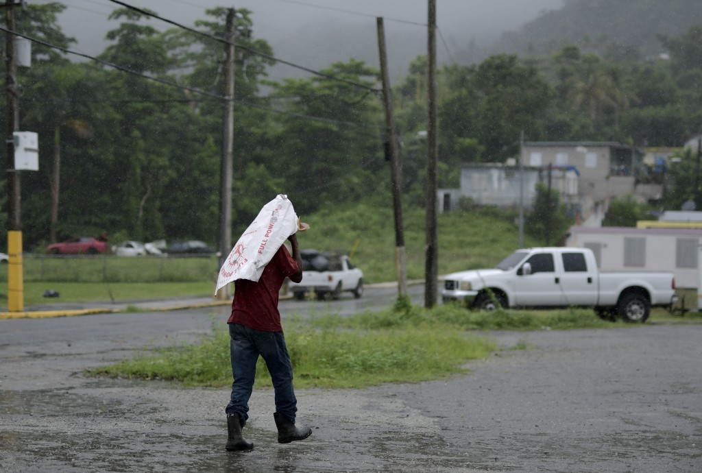 A man uses a flour bag to protect himself from the rain, in Yabucoa, Puerto Rico, Tuesday, Sept. 24, 2019. Tropical Storm Karen regained strength as i...