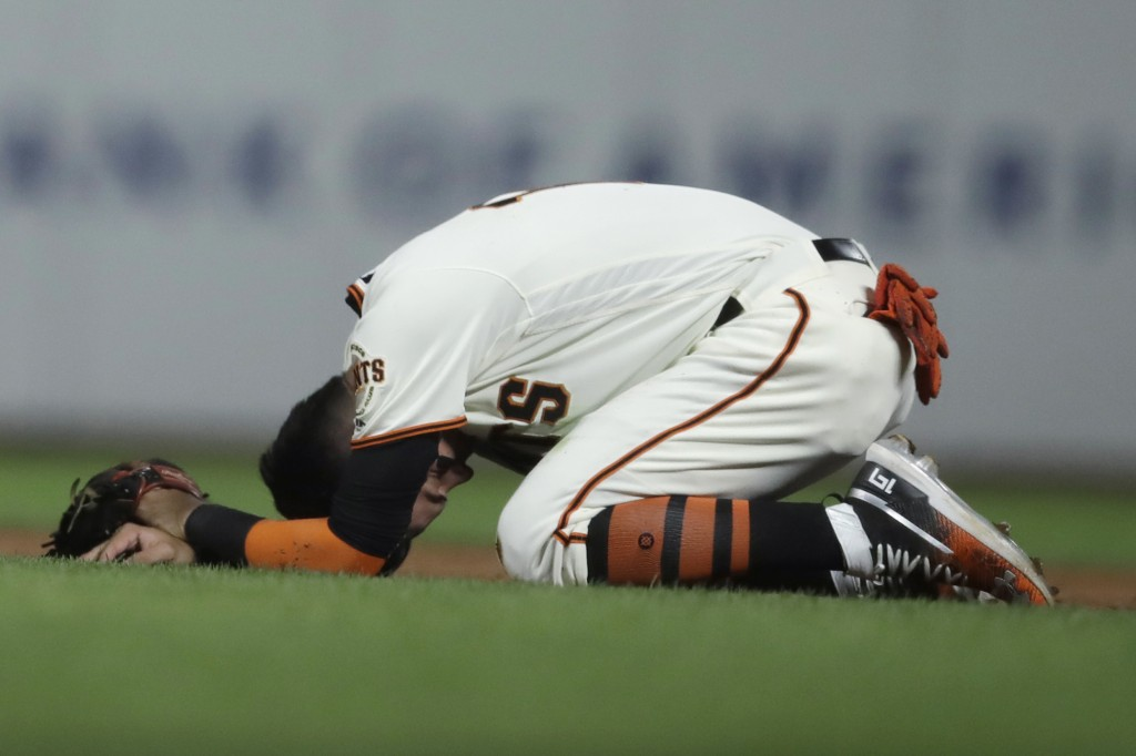 San Francisco Giants' Mauricio Dubon kneels on the field after colliding with Colorado Rockies' Tony Wolters during the seventh inning of a baseball g...