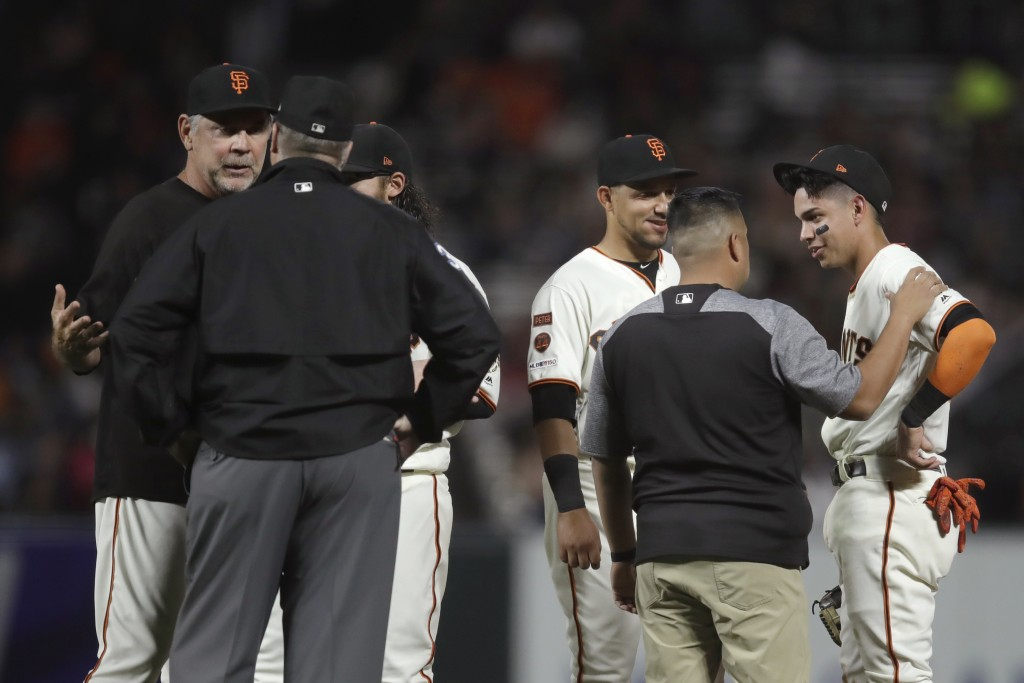 San Francisco Giants' Mauricio Dubon, right, speaks with a trainer after colliding with Colorado Rockies' Tony Wolters during the seventh inning of a ...