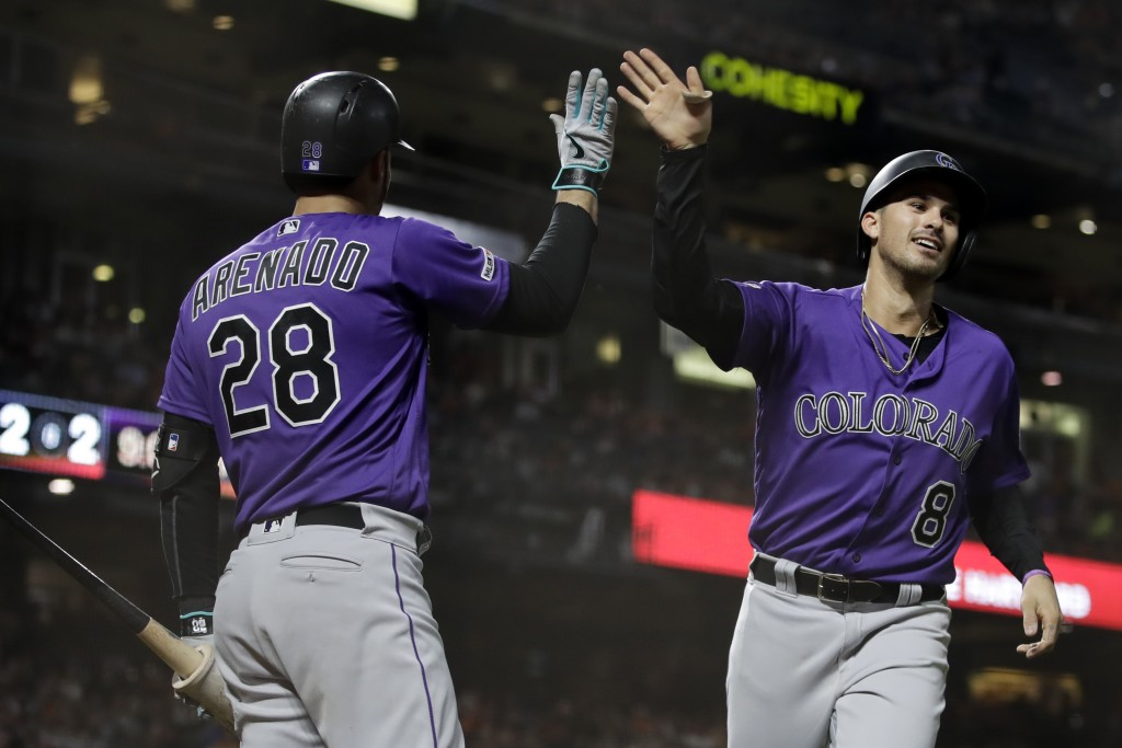 Colorado Rockies' Josh Fuentes, right, celebrates with Nolan Arenado (28) after scoring against the San Francisco Giants during the seventh inning of ...