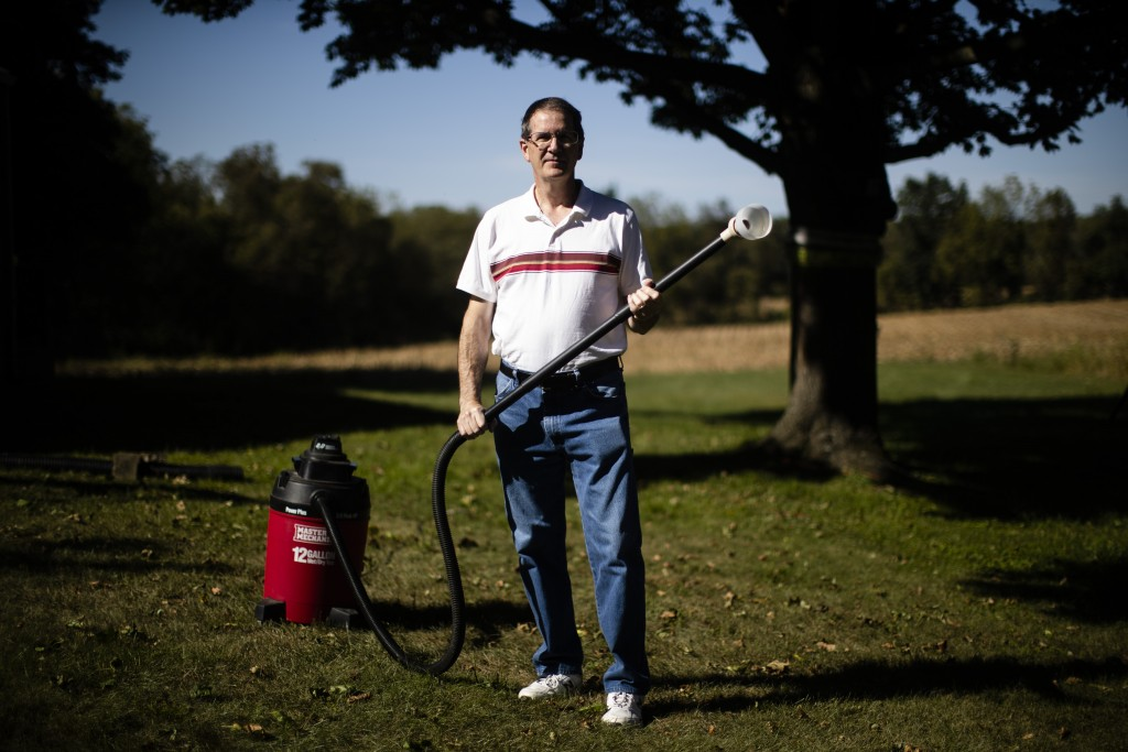 In this Thursday, Sept. 19, 2019, photo, Jim Wood poses for a photograph with his wet/dry vac he uses to deal with the swarms of lanternflies that hav...