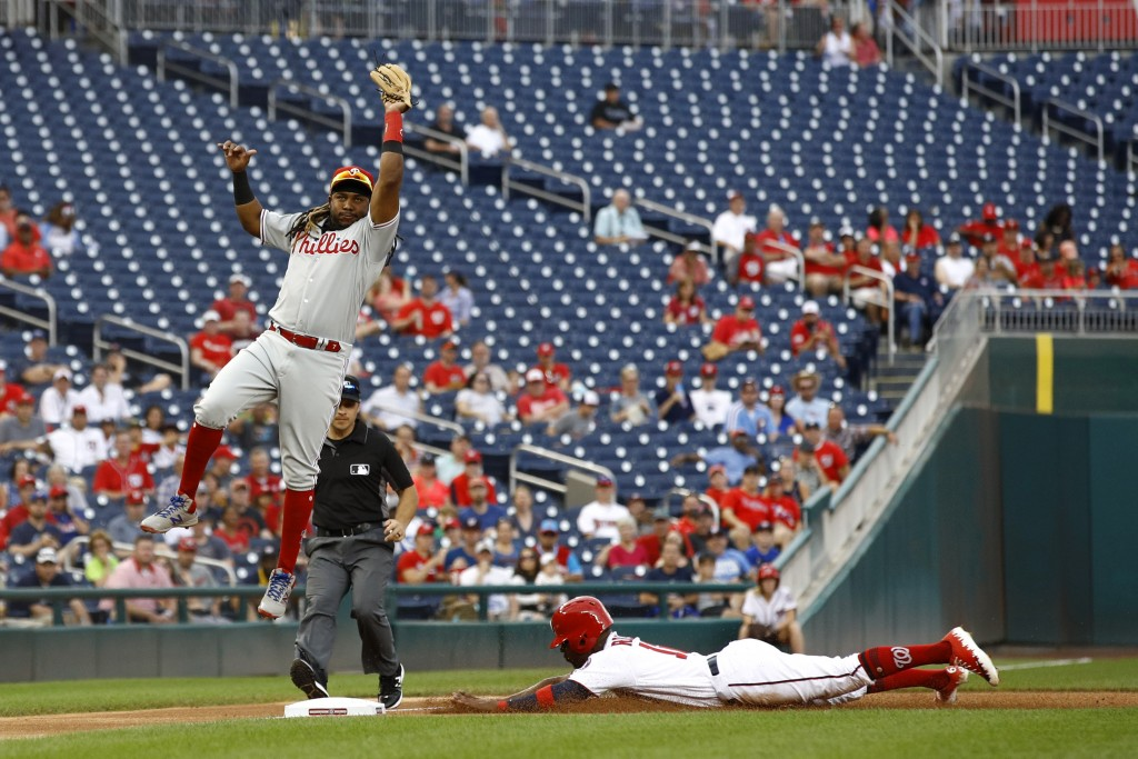 Washington Nationals' Victor Robles, bottom right, safely steals third base in front of Philadelphia Phillies third baseman Maikel Franco in the first...