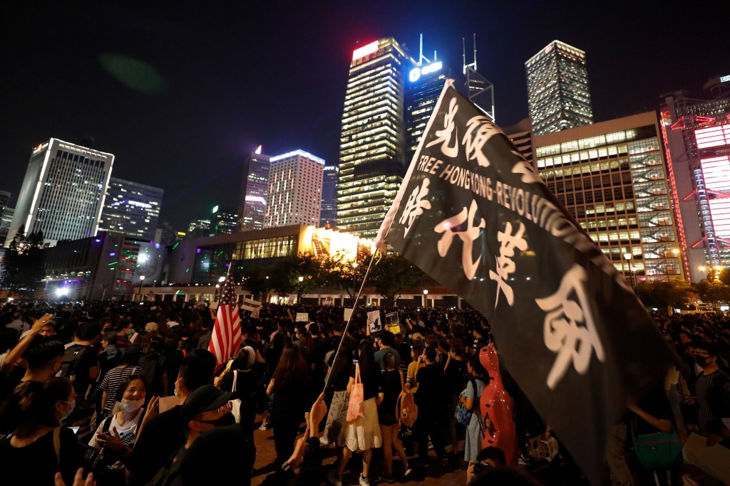 Protesters hold a placard and an American flag stage a rally at Edinburgh Place in Hong Kong, Friday, Sept. 27, 2019. Hong Kong police said Friday tha...