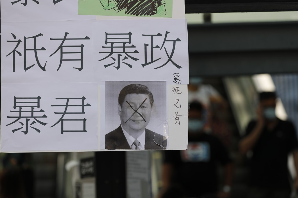 """A defaced poster of Chinese President Xi Jinping with part of a message that reads """"There are no rioters, there is only trranny,"""" stands on a new Lenn..."""