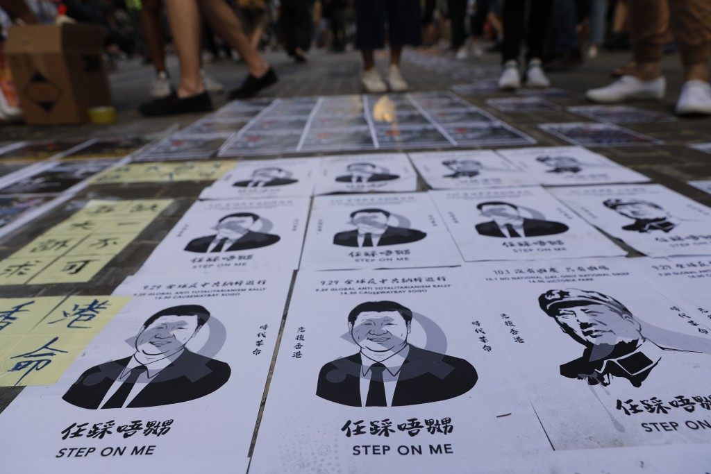 Posters of Chinese President Xi Jinping lay stuck on the ground as part of a newly created Lennon Wall in Hong Kong, Saturday, Sept. 28, 2019. Hong Ko...
