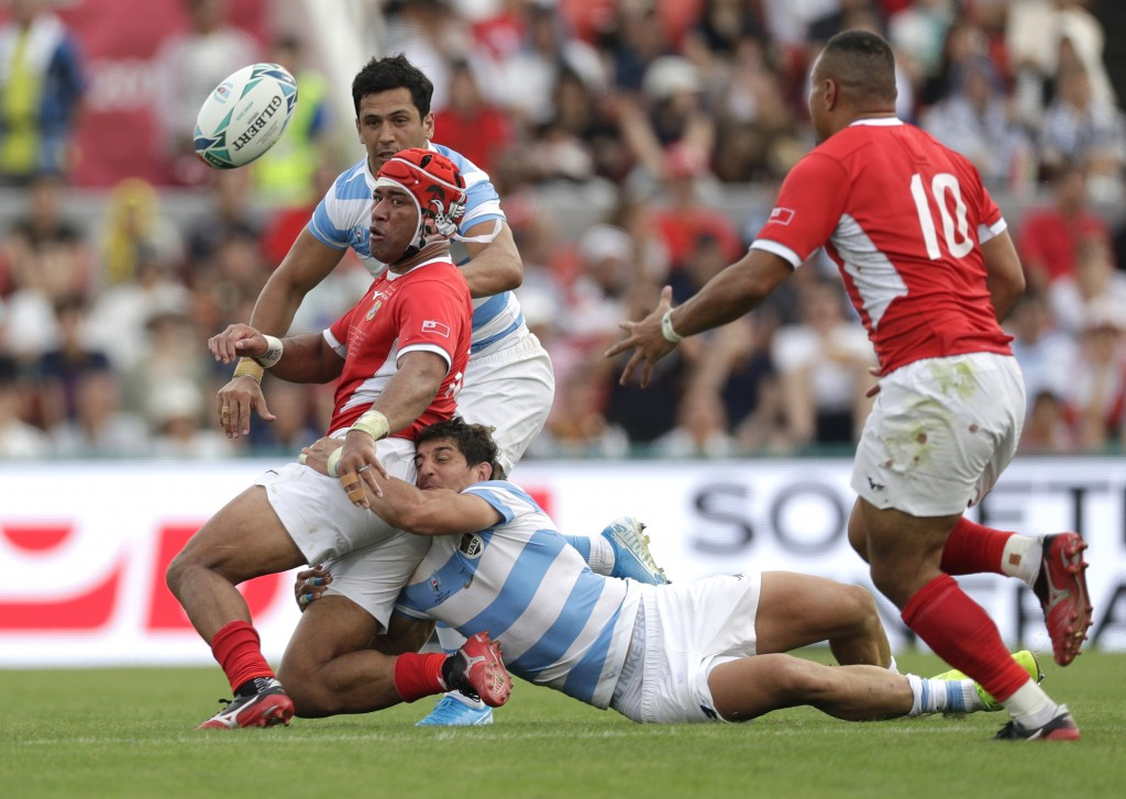 Tonga's Siale Piutau passes the ball to teammate James Faiva, right, as he is tackled by Argentina's Tomás Cubelli during the Rugby World Cup Pool C g...