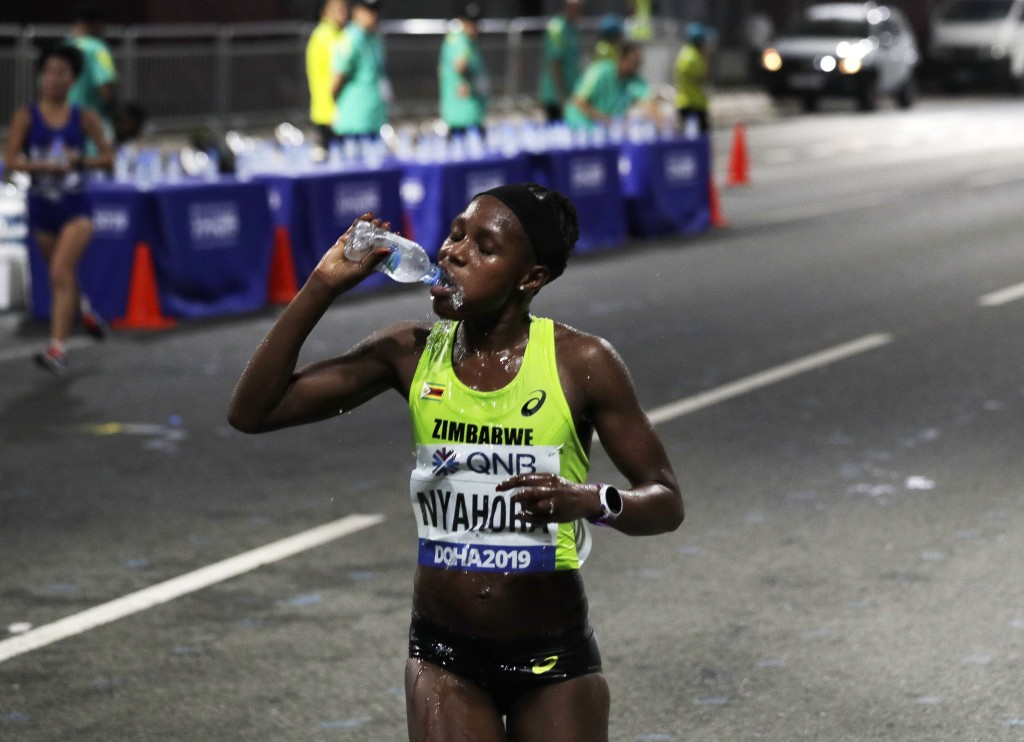 Rutendo Joan Nyahora, of Zimbabwe, drinks water during the women's marathon at the World Athletics Championships in Doha, Qatar, Saturday, Sept. 28, 2...