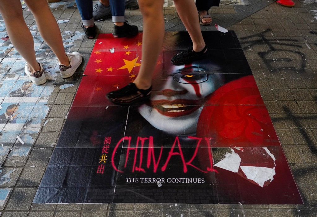 Pedestrians step on a caricature of Hong Kong Chief Executive Carrie Lam, part of a newly created Lennon Wall in Hong Kong, Saturday, Sept. 28, 2019. ...