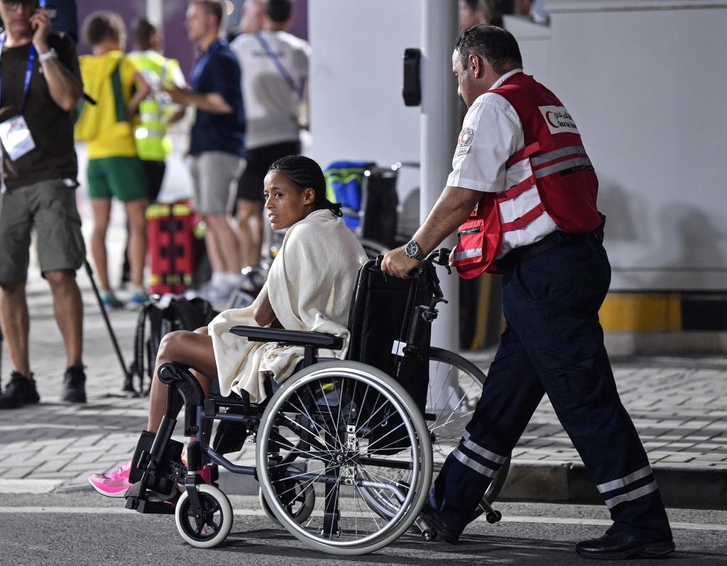 An unidentified competitor is transported by wheelchair after abandoning the women's marathon at the World Athletics Championships in Doha, Qatar, Sat...