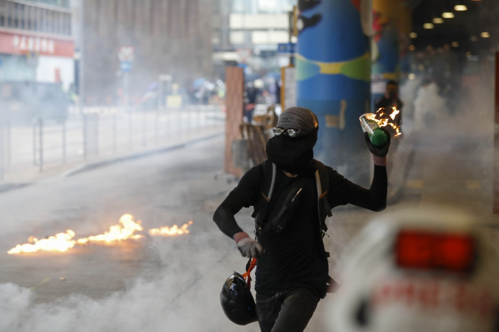A protestor prepares to throw molotov cocktail in Hong Kong, Sunday, Sept. 29, 2019. Riot police fired tear gas Sunday after a large crowd of proteste...