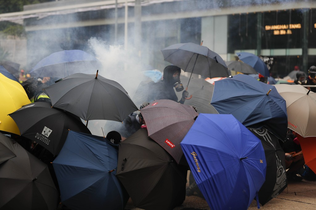 Protestors use umbrellas as shield as they face tear smoke from police in Hong Kong, Sunday, Sept. 29, 2019. Riot police fired tear gas Sunday after a...