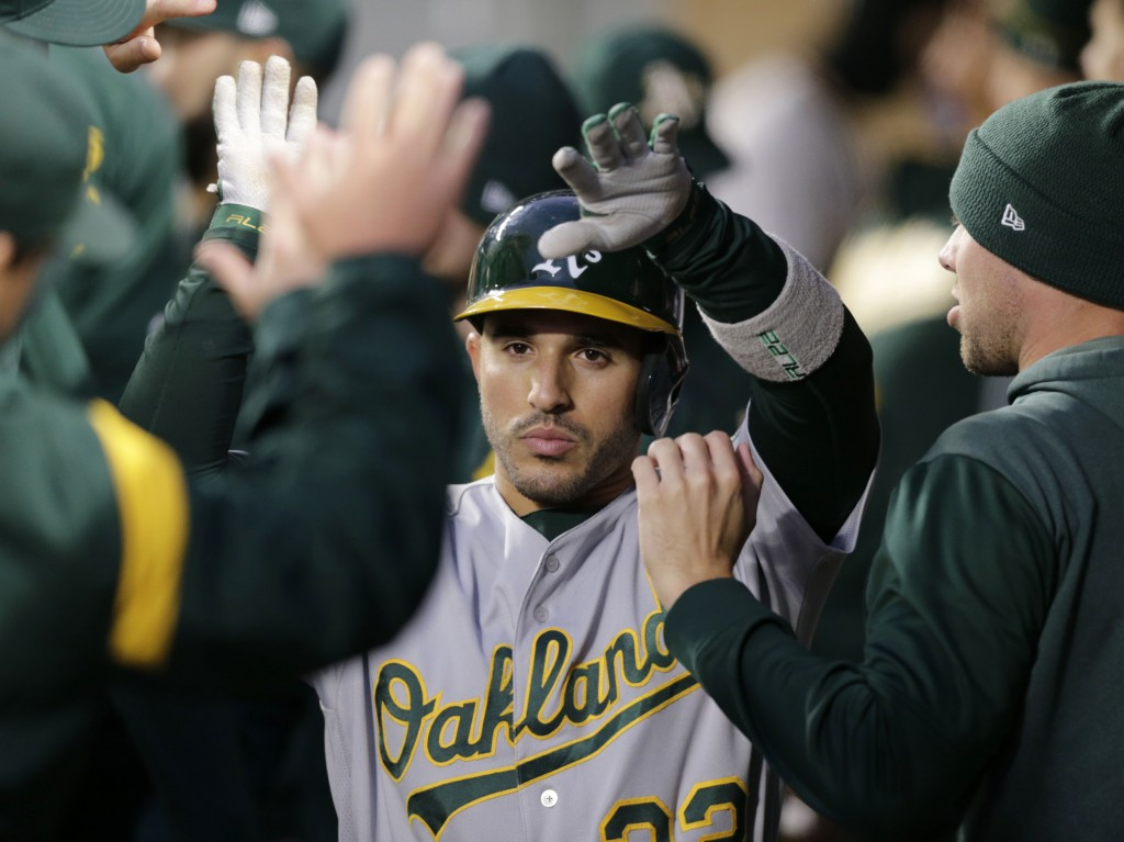 Oakland Athletics' Ramon Laureano makes his way through the dugout after hitting a solo home run on a pitch from Seattle Mariners' Marco Gonzales duri...