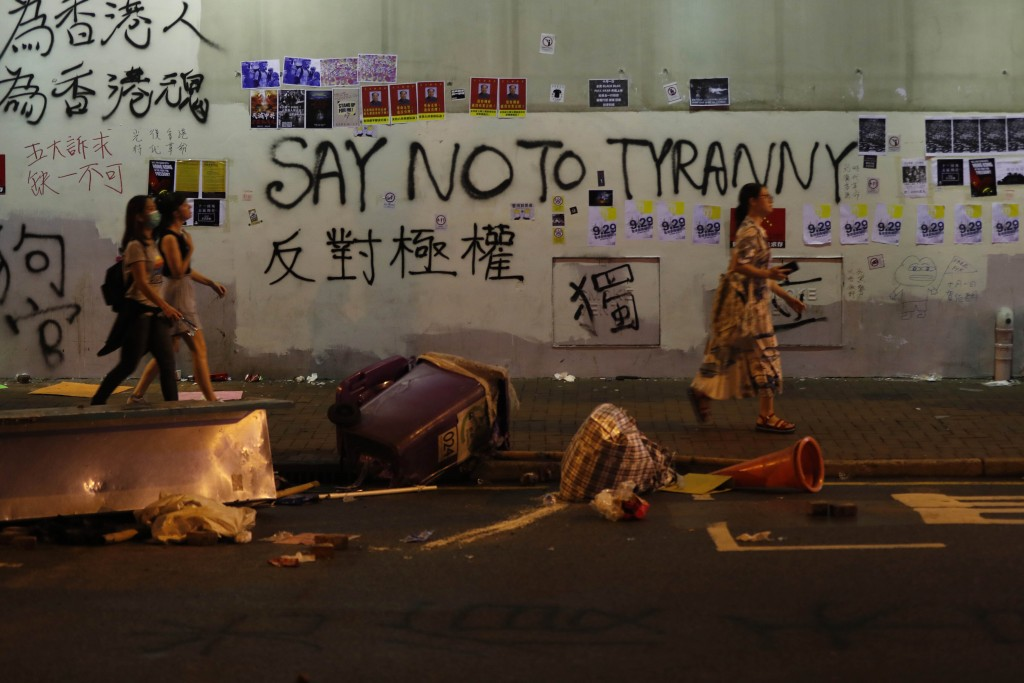 People walk past a wall with graffiti in Hong Kong, Sunday, Sept. 29, 2019. Protesters and police clashed in Hong Kong for a second straight day on Su...