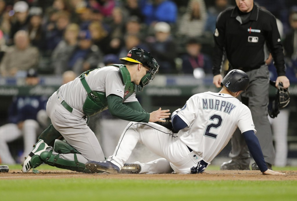 Seattle Mariners' Tom Murphy is tagged out at home by Oakland Athletics catcher Sean Murphy trying to score during the fifth inning of a baseball game...