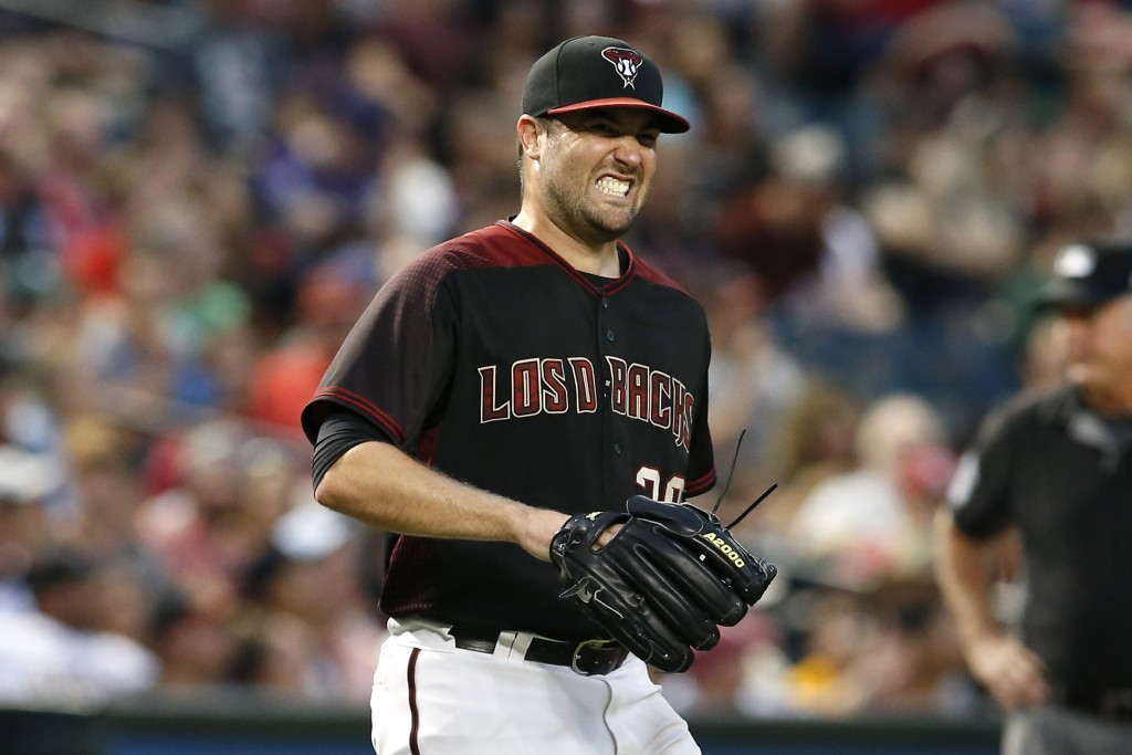 Arizona Diamondbacks starting pitcher Robbie Ray winces in pain after getting hit by a line drive off the bat of San Diego Padres' Manuel Margot durin...