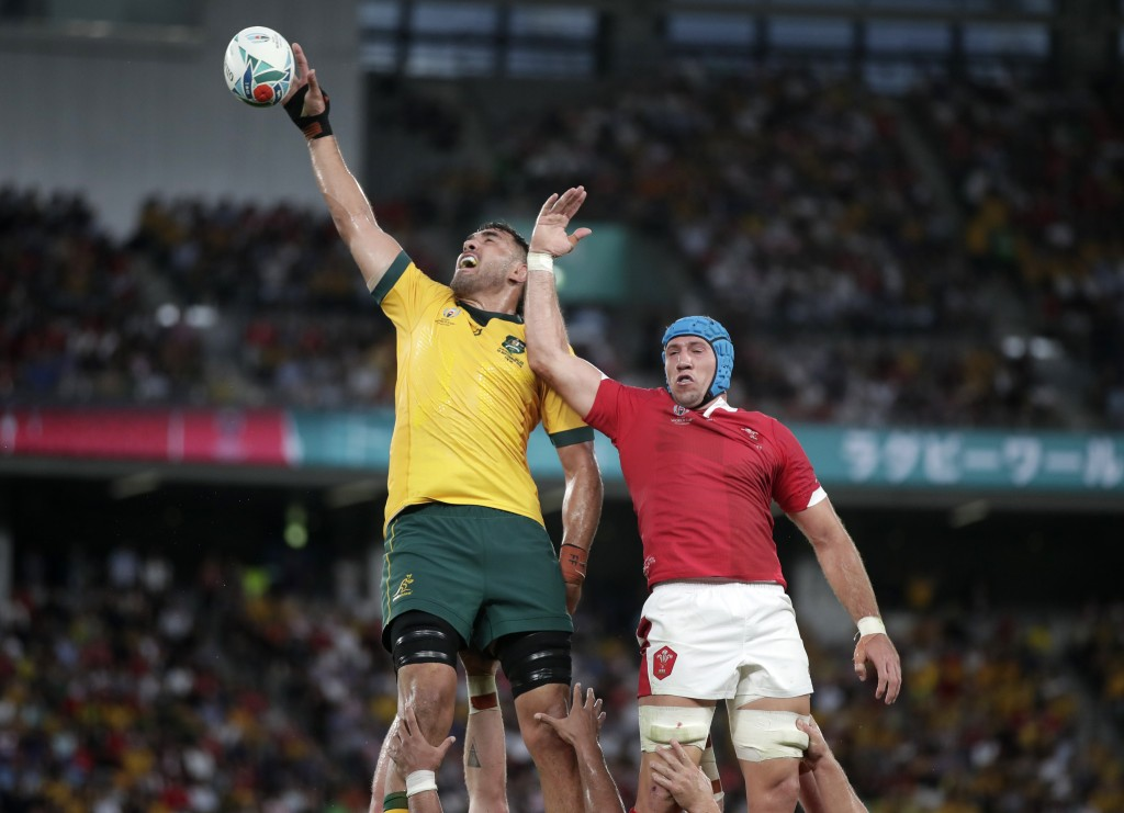 Australia's Rory Arnold, left, leaps above Wales Justin Tipuric to win lineout ball during the Rugby World Cup Pool D game at Tokyo Stadium between Au...