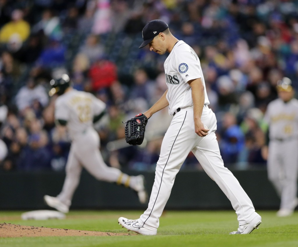 Seattle Mariners starting pitcher Marco Gonzales walks to the mound with Oakland Athletics' Ramon Laureano rounding the bases behind after hitting a s...