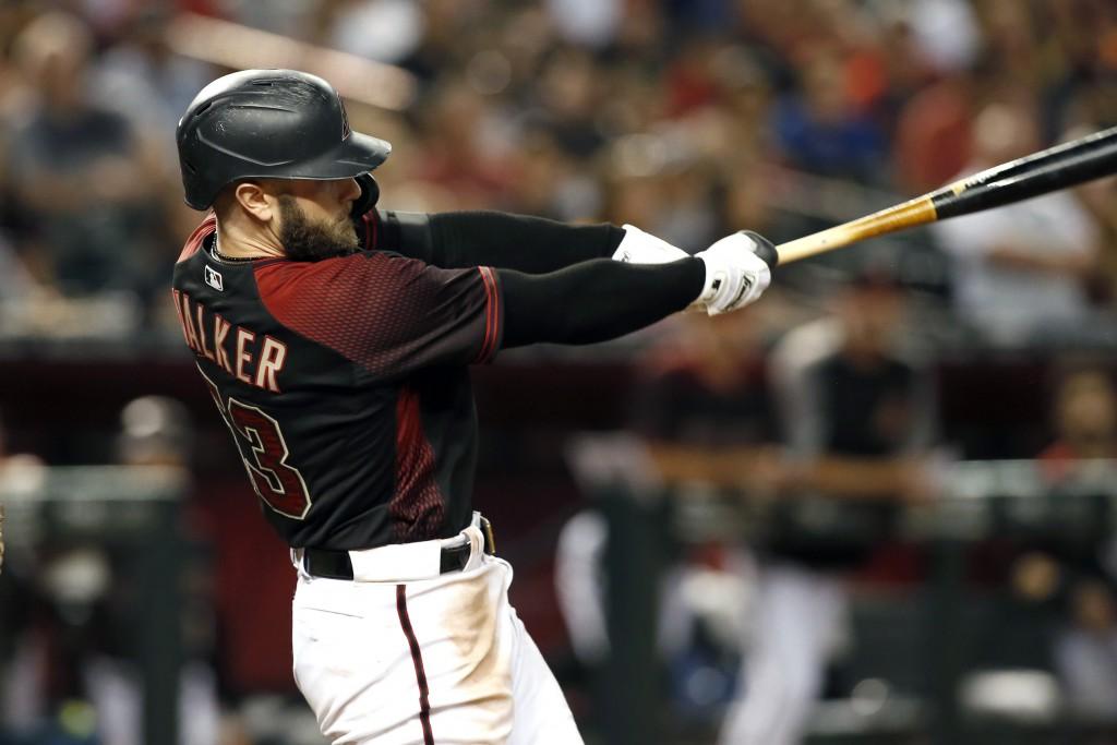 Arizona Diamondbacks' Christian Walker follows through on his swing as he hits a grand slam home run against the San Diego Padres during the seventh i...