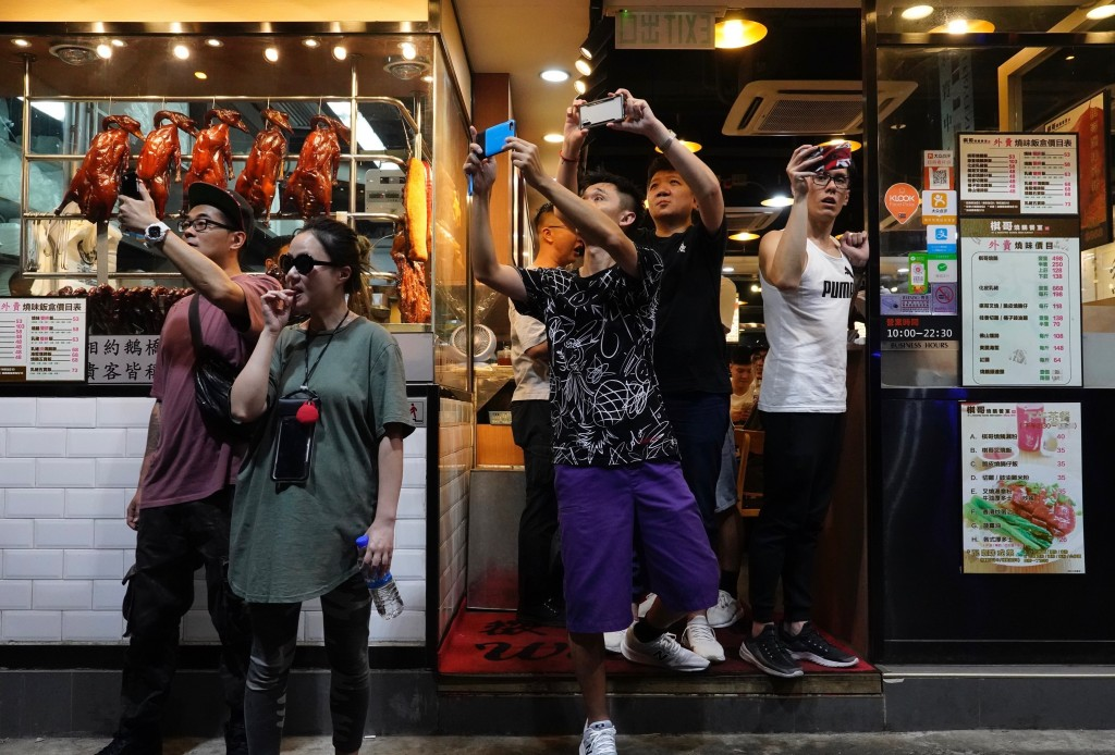People at a restaurant take pictures of police water cannons in Hong Kong, Sunday, Sept. 29, 2019. Protesters and police clashed in Hong Kong for a se...