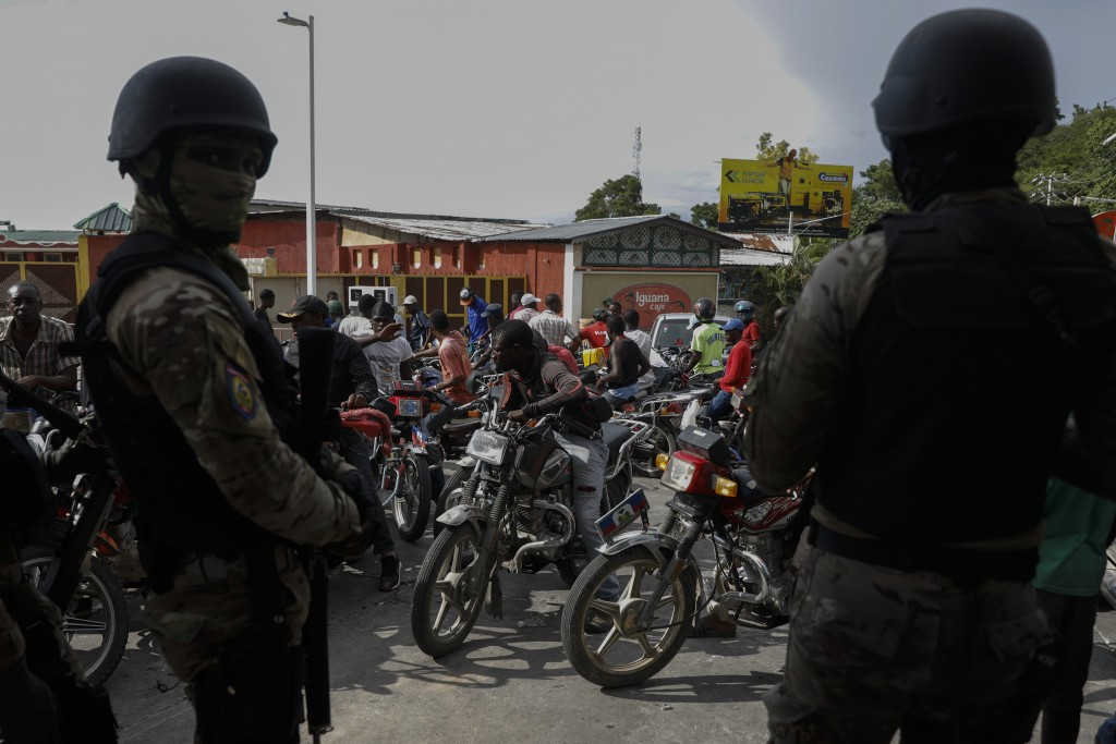 Police officers wait to have their truck filled with gas at one of the few open service stations, where car and motorcycle drivers were waiting in lin...