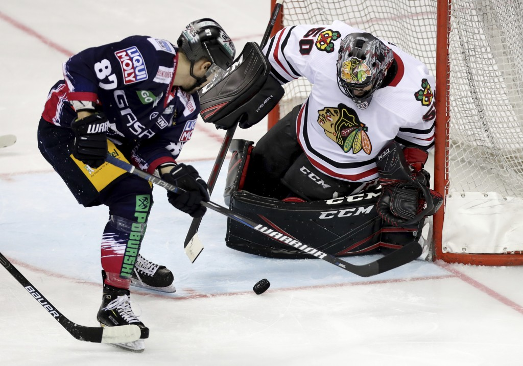 Chicago's Corey Crawford, right, saves a shot by Berlin's Fabian Dietz, left, during a NHL Global Series ice hockey game between Eisbaeren Berlin and ...